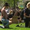 Un groupe de jeunes posent le genoux par terre, signe de solidarité envers les personnes racisées victimes de violence policière.