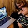 Un enfant en pyjama sur les genoux de sa mère qui écoute la radio avec des écouteurs.