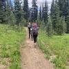Deux randonneurs marchent le long d'un sentier en forêt dans le parc provincial Manning en Colombie-Britannique.