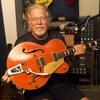 Randy Bachman montre une guitare orange de style western.