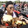 Photo d'un homme qui tient un trophée de couleur or à côté de partisans qui prennent sa photo.