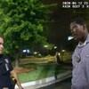 Un homme noir parle les bras levés, un téléphone portable dans une main, face à un policier.