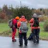 Trois personnes avec de l'équipement et des vêtements chauds se préparent à une battue.