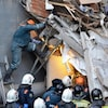 L'équipe de secours, dont un dans une échelle, à travers des débris.
