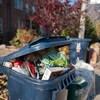 Un bac de recyclage au couvercle entrouvert tellement il déborde placé pour la collecte sur le trottoir.
