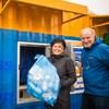 Josie Osborne, un sac plein de bouteilles à la main, et Allen Langdon posent fièrement devant le conteneur où il est possible de retourner ses bouteilles.