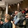 Des gens assis applaudissent dans la salle du conseil municipal.