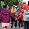 Photo d'enfants qui se tiennent la main en marchant vers l'entrée de leur école avec leurs sacs à dos.