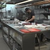Un employé à l'œuvre dans la cuisine du restaurant Chez Rioux & Pettigrew.
