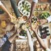 Des gens trinquent devant une table pleine de plats.