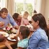 Des adultes et des enfants mangent autour d'une grande table.