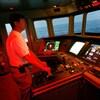 Un homme en chemise contrôle un navire à l'aide de commandes de barre physiques.
