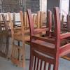Des chaises renverses sur des tables dans un restaurant fermé.