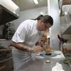 Un chef prépare une assiette dans une cuisine de restaurant.