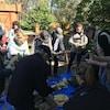 Des participants réunis autour d'une table extérieure épluchent des épis de maïs.