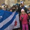 Un drapeau franco-albertain en premier plan et des enfants tenant des petits drapeaux.