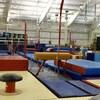 Des tapis de gymnastiques et d'autres appareils sont répartis sur deux terrains de tennis intérieurs.
