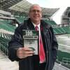 Un homme tient un livre dans un stade de football.