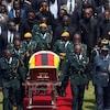 Des militaires transportent le cercueil. Des membres de sa familles suivent.