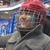Un jeune avec un casque de hockey, des gants et le baton à la main, sourit, des gradins en arrière-plan.