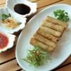 Une assiette avec 6 rouleaux de printemps posée sur une table en bois à côté de quelques sauces.