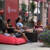Des gens sont assis sur des chaises et des coussins sur la rue Sparks.