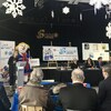 Une organisatrice est au micro pour donner les détails de la programmation aux gens présents à la conférence de presse.