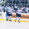 Deux joueurs de hockey reçoivent les félicitations de leurs coéquipiers devant le banc des joueurs.