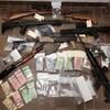 Des armes à feu de gros calibre et d'importantes sommes d'argent disposées sur un plancher.