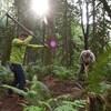 Deux hommes avec des outils de jardinage en plein milieu d'une forêt.