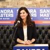 Portrait de Sandra Masters, mains posées sur un pupitre en bois, devant un micro.