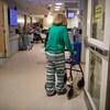 Une femme marche dans un corridor à l'aide d'un déambulateur.
