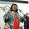 La femme chante devant un micro.