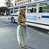 Carrie Bradshaw pose devant un bus.