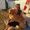 Sarah Sweet-Fortin, souriante, est assise dans un patio dans une cour avec un chien sur les genoux.