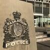 Les armoiries du Service de police de Saskatoon, devant l'édifice de ce Service, avec la porte et les escaliers.
