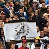 Des partisans brandissent le drapeau des Schooners dans les estrades du Stade de Moncton, lors d'un match entre les Argonauts et les Eskimos en septembre 2010.