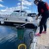 Une femme soulève un filet avec des déchet en plastique sur un quai.