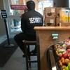 Un homme assis sur un tabouret à l'intérieur d'un supermarché.
