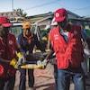 Des travailleurs paramédicaux de la Croix-Rouge tiennent une civière après le séisme en Haïti.