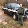L'agent de conservation du Nouveau-Brunswick Denis Léger est debout devant sa camionnette de service dans un sentier boueux.