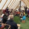 Des dizaines d'élèves écoutent une enseignante sous une tente.