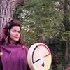 Une femme tient un tambour dans sa main.