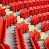 Des rangées de sièges rouges dans un stade séparées par une allée.