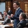Simon Jolin-Barrette debout à l'Assemblée nationale, aux côtés du premier ministre François Legault et du ministre François Bonnardel, qui sont assis.