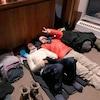 Deux skieurs couchés au sol, à l'intérieur du chalet du sommet, sourient au photographe.