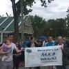 Un groupe de gens tient une pancarte où il est écrit « marche pour la SLA ».