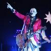 Le chanteur s'adresse à la foule guitare en main et doigt dans les airs.