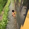Une jeune femme en maillot de bain s'agrippe à un train en mouvement.