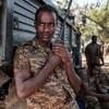 Un soldat éthiopien appuyé sur la boîte d'un camion tient un émetteur-récepteur portatif dans ses mains.